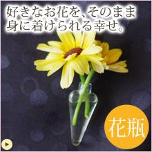 小さなガラスの花瓶。ピンバッチで服や小物につけて、生花を身に着けられます。