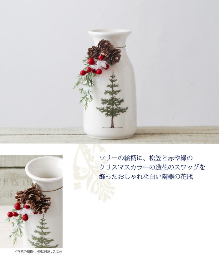 ツリーの絵柄に、松笠と赤や緑のクリスマスカラーの造花のスワッグを飾ったおしゃれな白い陶器の花瓶
