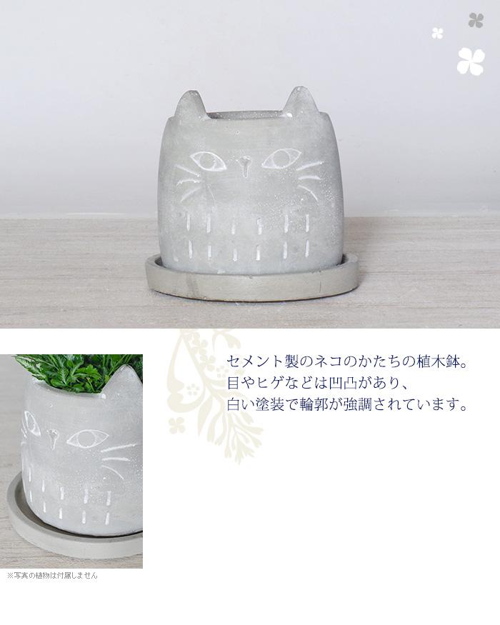 セメント製のネコのかたちの植木鉢。目やヒゲなどは凹凸があり白い塗装で輪郭が強調されています。