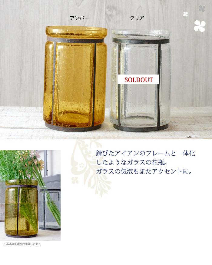 錆びたアイアンのフレームと一体化したようなガラスの花瓶。ガラスの気泡もまたアクセントに。